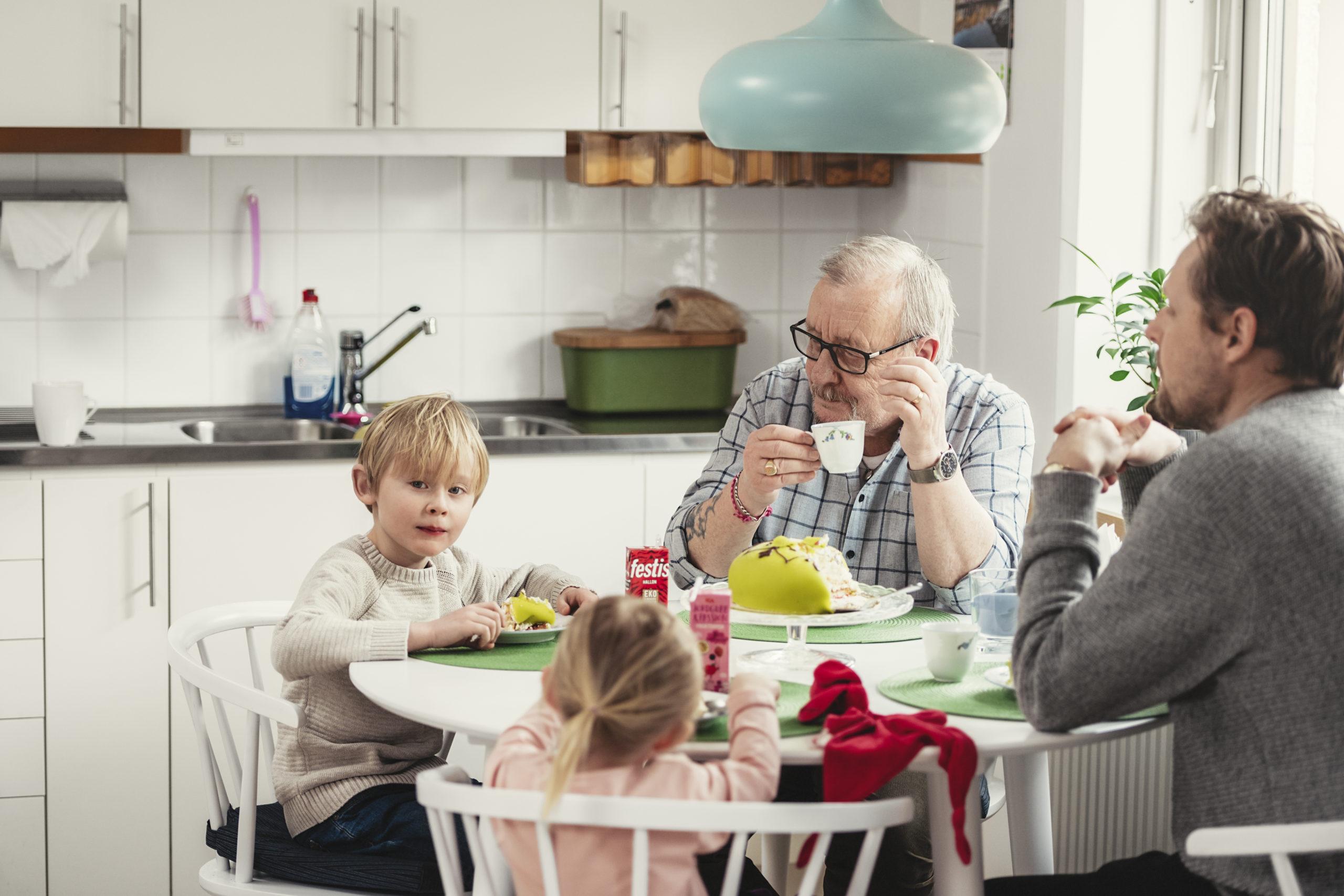 http://Hyresgäst%20sitter%20med%20barn%20och%20barnbarn%20vid%20köksbordet%20och%20fikar